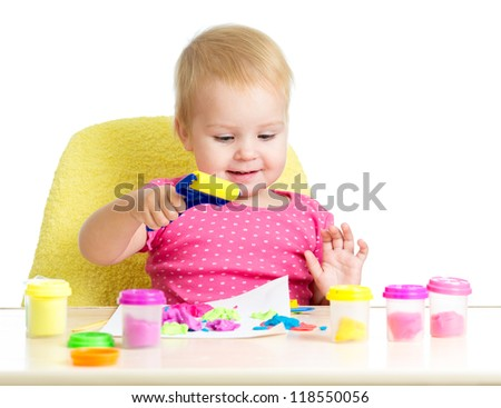 Little kid sitting at table playing with colorful clay - stock photo