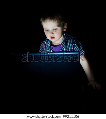 Little kid using laptop by night - stock photo