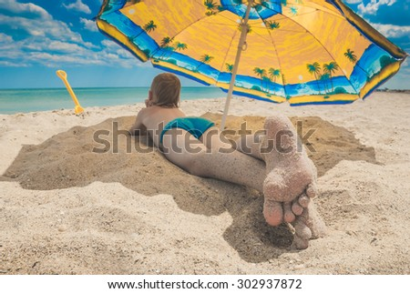 Little kid with feet in send lying on a sandy beach under umbrella - stock photo