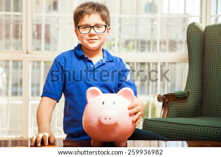 Little kid with glasses holding all of his savings in a piggy bank at home - stock photo