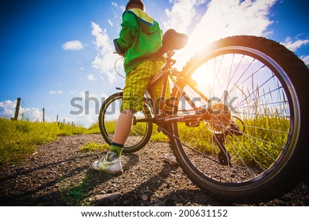 little kid with his bicycle in the field - stock photo