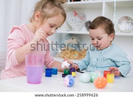 little kids  painting eggs for Easter - stock photo