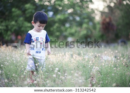 Little kids playing alone with nature background - stock photo