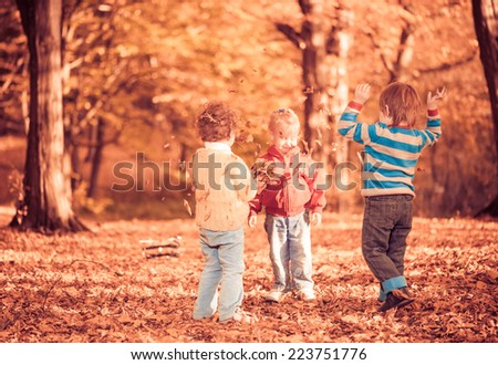 little kids playing with faded fall season forest leafs - stock photo