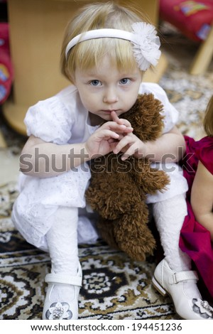 little kinder garden girl in white dress sitting on the carpet with toy bear - stock photo