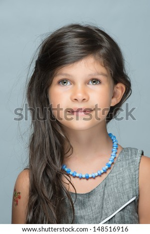 Little lady with gorgeous eyes and innocent expression - stock photo