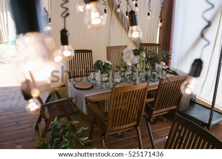 Little lamps hang over wooden dinner tables in the hall