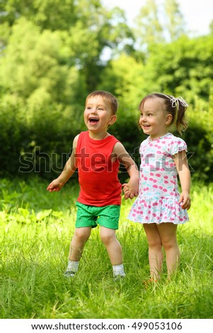Little laughing girl and boy stand on fresh green grass in park