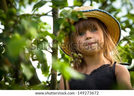 Little lovely girl posing in a straw hat in the park - stock photo