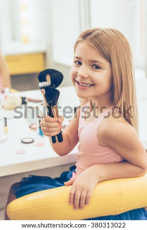 Little make-up artist. Cheerful little girl holding make-up brushes and looking at camera with smile whilesitting at the dressing table - stock photo