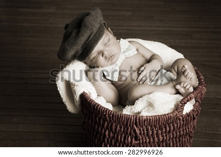 Little Man.  Adorable mixed race newborn wearing a hat and bow tie fast asleep in a basket.  Desaturated to give it a vintage feel.  Room for your text. - stock photo
