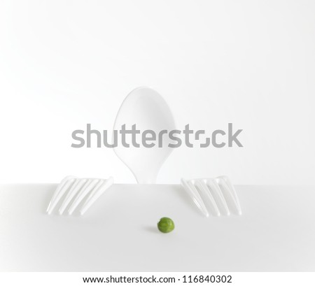 Little man eats pea - stock photo
