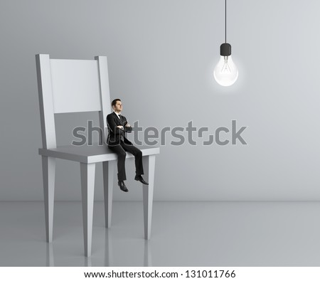 little man sitting a big chair and lamp - stock photo