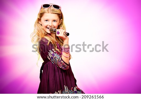 Little modern girl in beautiful dress singing into a microphone over pink background.  - stock photo