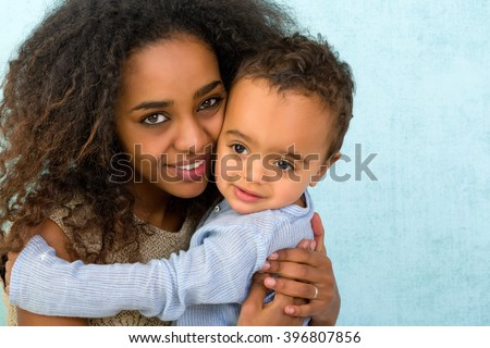 Little 18 month old African boy hugging his mother - stock photo