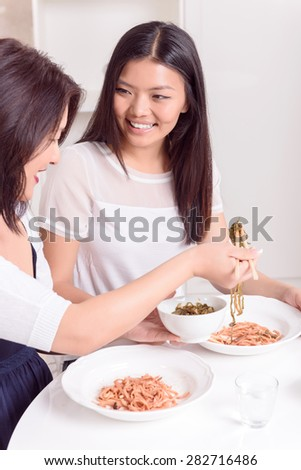 Little more.  Two girls eating Asian food at home - stock photo