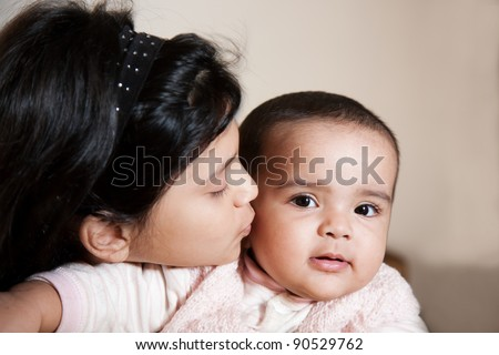 little muslim girl kissing her sister while holding her in the lap - stock photo