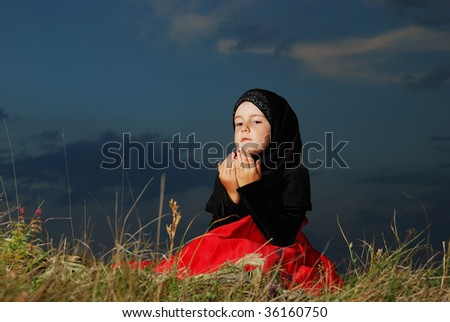 Little muslim girl on meadow, before sunset - stock photo