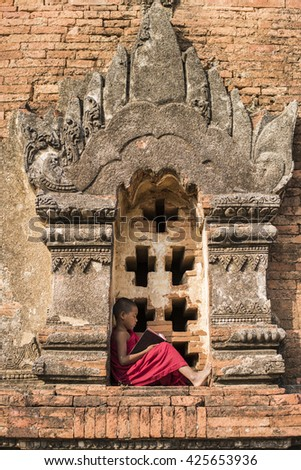 Little Myanmar monk reading book, sitting outside monastery,  - stock photo