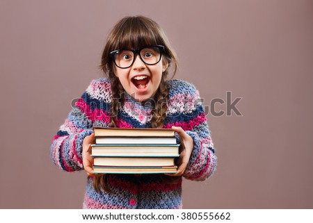 Little nerdy girl is holding books and she is very excited because she is going to learn.I can't wait to learn! - stock photo
