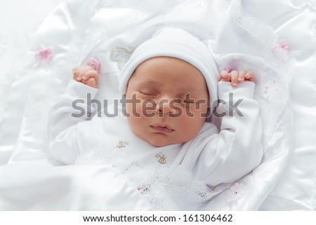 Little Newborn Angel Sleeping over His White Bed - stock photo