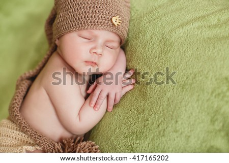 Little newborn baby boy 7 days, sleeps. newborn baby curled up sleeping on a blanket. Eight day old smiling newborn baby boy.