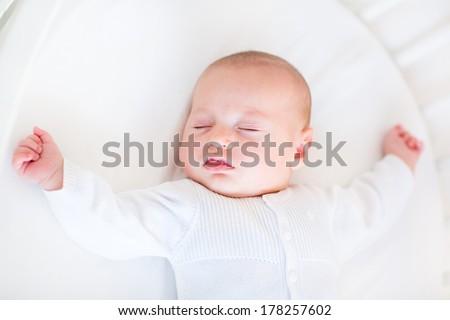 Little newborn baby boy sleeping in a white round crib  - stock photo