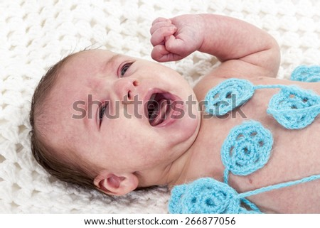 Little newborn baby lying on a white knitted scarf and cries - stock photo