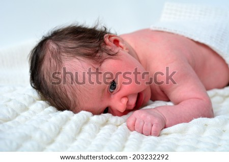Little newborn baby (4 week old) laying on soft blanket, awake. side view