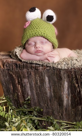 Little newborn dressed up as frog and sleeping on a tree stump - stock photo