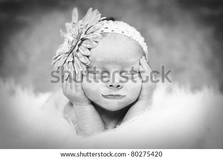 Little newborn in art type pose. Appears to be smiling in her sleep