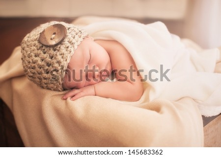 Little newborn sleeping in a wooden box - stock photo