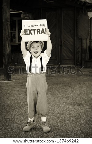 "Little newsboy holding up a newspaper and shouting ""Extra!"""