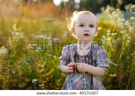 Little nice sweet baby walking in a meadow
