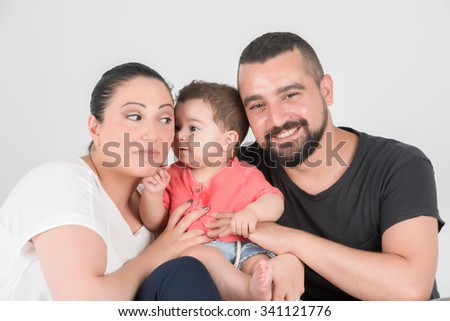 Little one whispering on his mothers ear and posing all together - stock photo