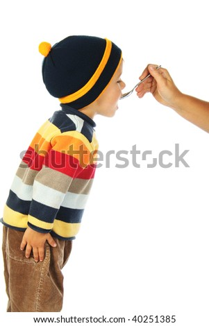 little open-mouthed boy in the sweater with spoon held by the adult person's hand - stock photo