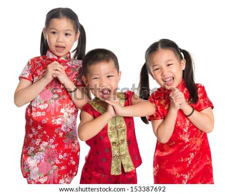 Little oriental children wishing you a happy Chinese New Year, with traditional Cheongsam standing isolated on white background. - stock photo