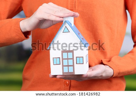 Little paper house in hand close-up, on bright background - stock photo