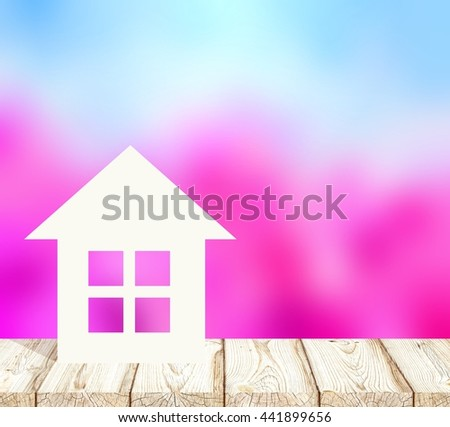 Little paper house is on wooden surface of table or floor. Behind a blooming spring garden blur background. Like cherry or apple trees. Blue cloudless sky. Housing in the fresh air. 3d illustration