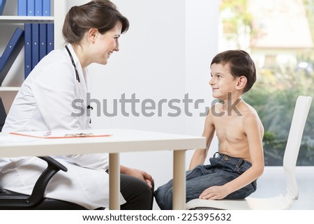 Little patient talking with child's doctor - stock photo