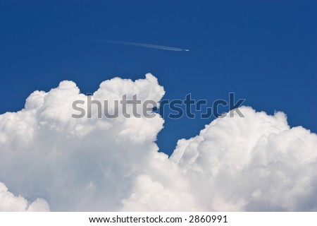 Little plane and big cloud in a blue sky