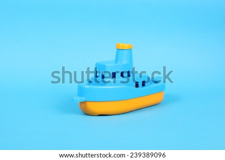 little plastic toy ship on the blue background - stock photo