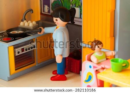 Little plastic toys. Mom prepares to eat - stock photo