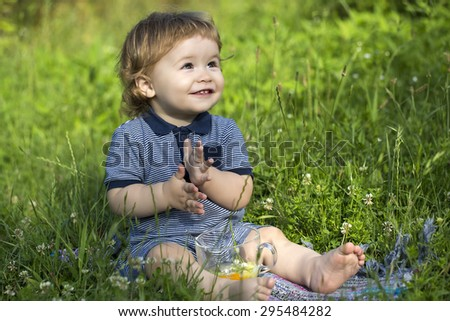 Little playful happy smiling baby boy sitting in field on fresh green grass with glass cup, horizontal picture - stock photo