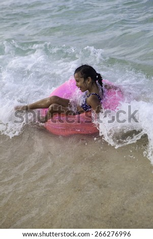 little polynesian girl on her pink float ring in the ocean - stock photo