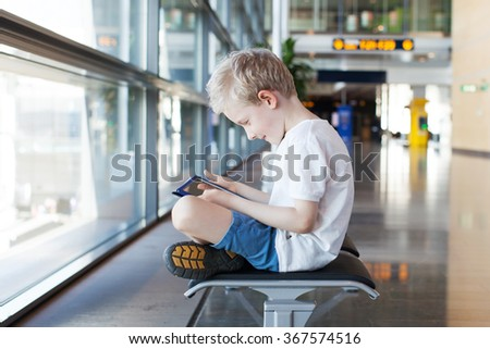 little positive boy holding tablet computer and waiting at the airport - stock photo