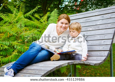 Little preschool boy and his mother sitting on bench in park and reading fairytale book together. Happy kid and mum spending time together. - stock photo