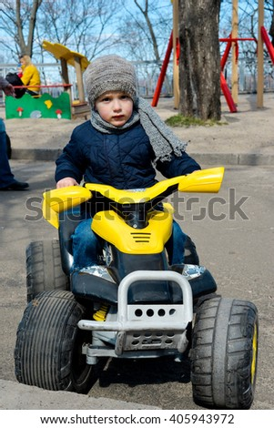 Little preschool boy driving big toy car, playing and having fun, outdoors. Little racer playing in the park. - stock photo