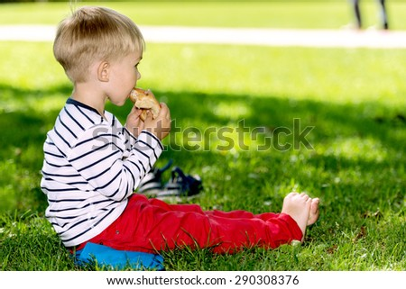 Little preschool boy eating, outdoors. - stock photo