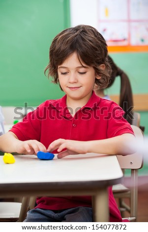 Little preschool boy molding clay at desk in classroom